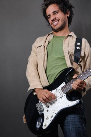 Portrait of young trendy man playing electric guitar photo