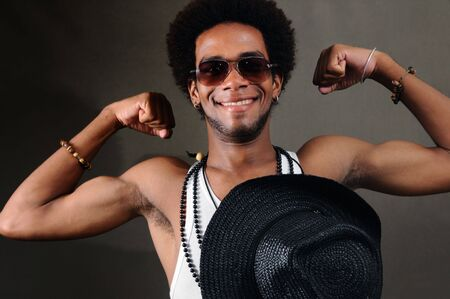 Portrait of young trendy african american man showing his muscles photo