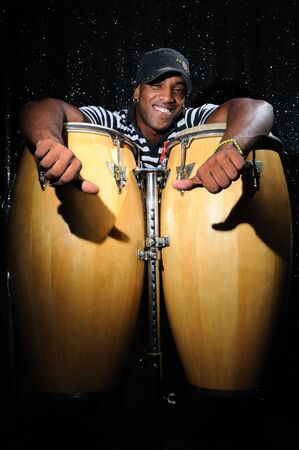 percussionist: Portrait of young latino percusionist playing african drums Stock Photo