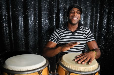 Portrait of young latino percusionist playing african drums Stock Photo