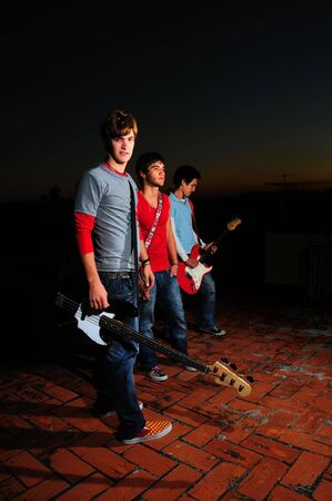 Portrait of young trendy musiciands holding instruments photo
