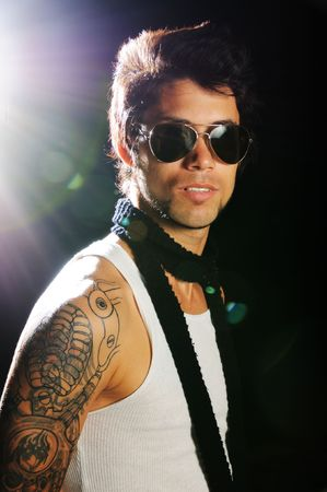 Portrait of young male fashion model with arm tattoo and sunglasses Stock Photo