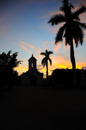 Silhouette of church and royal palm trees against sunset sky in Trinidad, cuba. photo