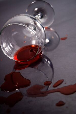 Spilled Red wine and cork with bottle and a glass on the background