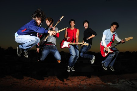 Portrait of young trendy teenager group jumping with musical instruments photo