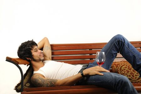 Portrait of a young man reclining over a bench with glass of wine photo