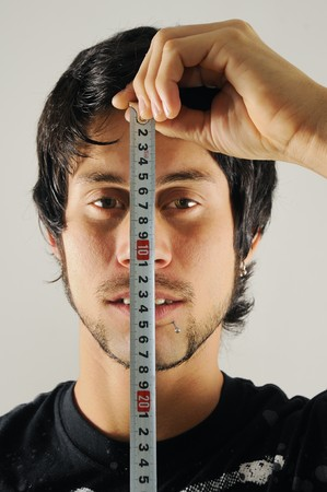 Portrait of a young man with measure tape measuring his face