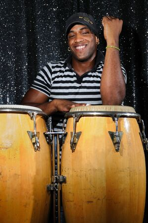 african drums: Portrait of young latino percusionist playing african drums Stock Photo