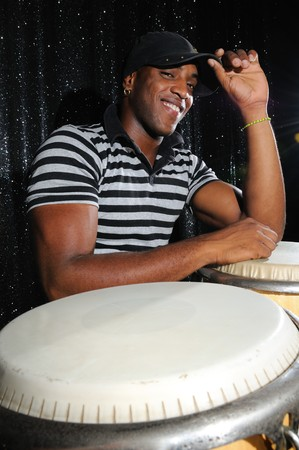 Portrait of young latino percusionist playing african drums photo