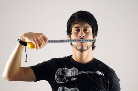 Portrait of a young man with measure tape measuring his face photo