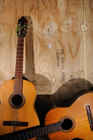 Two Old acoustic guitars against grunge aged surface Imagens