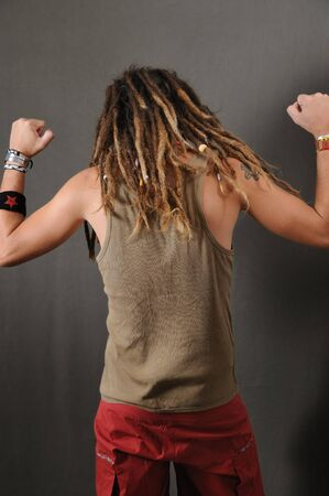 Back portrait of young funky male with long dreadlocks