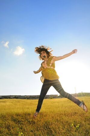 Portrait of young woman jumping of joy on yellow grass field photo