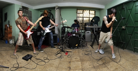 Group of young male musicians playing on messy garage