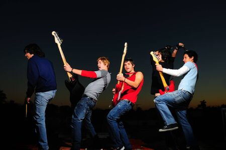 Portrait of young trendy group of musicians standing with instruments Stock Photo - 4343595