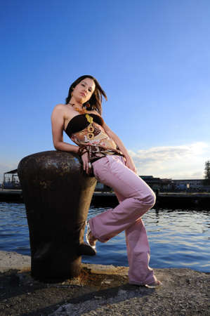 Portrait of young trendy fashion model posing on a pier photo