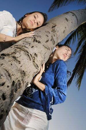 Portrait of two fashion women over tropical palm tree photo