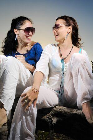 Portrait of two trendy young women having fun photo
