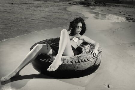 Portrait of young fashion female on the sand over tire photo