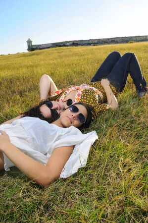 Portrait of two young girl friends lying on green grass field photo