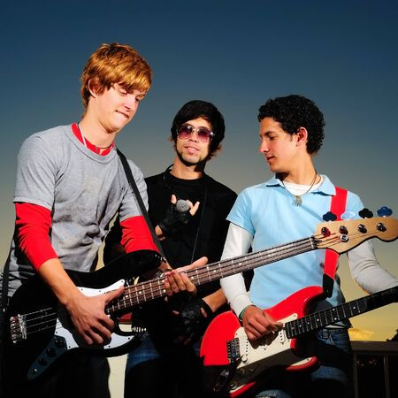 Portrait of young trendy musicians playing electric guitars photo