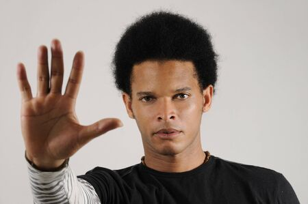 Portrait of young trendy african americn man doing stop sign with hand photo
