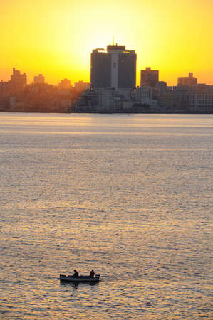 A view of havana skyline at sunset with fishing boat on the front Stock Photo - 4851779