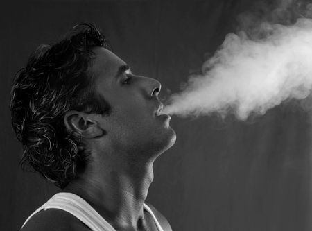man profile: Portrait of a young man exhaling smoke stack