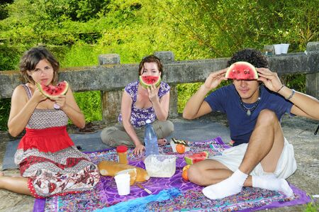 Young people in a picnic eating water melon photo