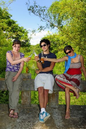Portrait of three young friends drinking beer in natural environment photo