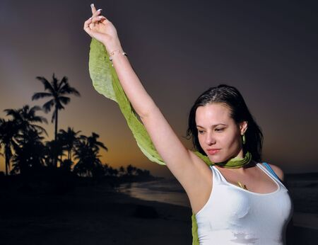 Portrait of young beauty posing at dusk on tropical beach photo