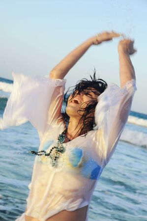 Portrait of young happy woman playing on beach waves photo