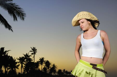 Portrait of young trendy hispanic woman wearing a hat on tropical beach background at sunset photo