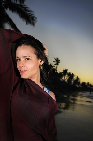 Portrait of young trendy hispanic woman on tropical beach background at sunset photo