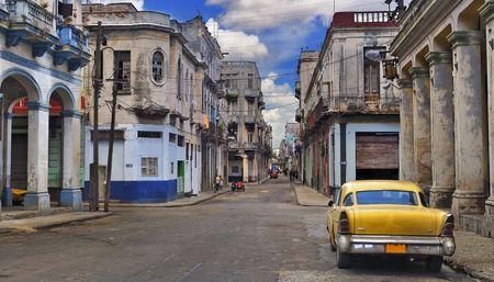 Vista panorámica de la calle de La Habana con edificios ruinosos y de autos clásicos antiguos Foto de archivo