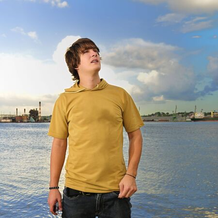 Portrait of trendy male teen looking up outdoors photo