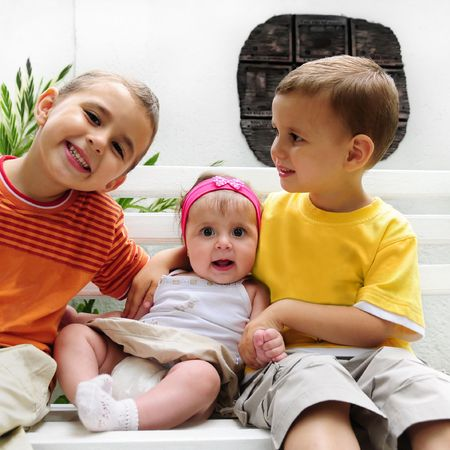 Portrait of two caucasian happy young boys with little baby girl sitting on a bench photo