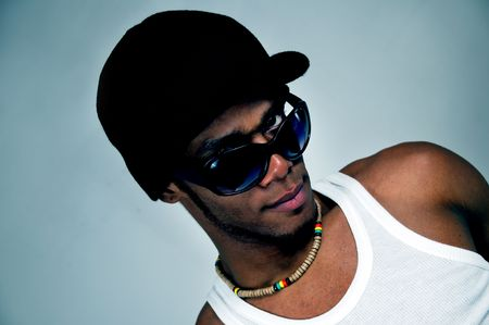 Portrait of young trendy african american man wearing cap and sunglasses with attitude