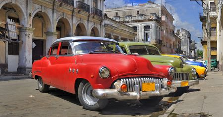 Old american classic cars parked in a street of havana city with crumbling buildings in the background