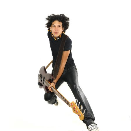 Portrait of young trendy guy jumping with electric bass guitar isolated on white photo