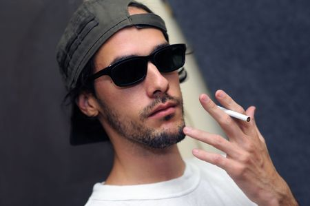 Portrait of young guy holding cigarette with cool look and sunglasses