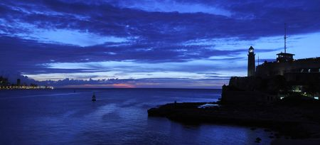Panoramic view of El Morro lighthouse and havana bay at dusk photo