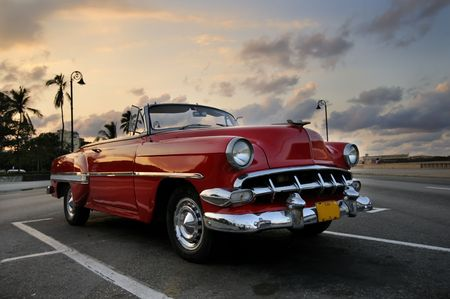 collector: View of red classic vintage american car parked in havana street against sunset sky