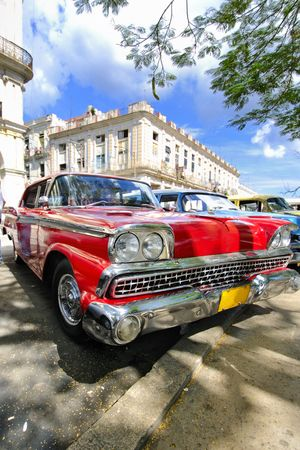 Old red car parked under tree branches in havana, cuba