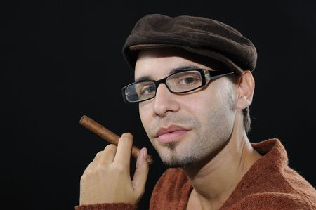 Portrait of young male model with eyeglasses holding cuban cigar - isolated on black photo