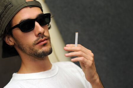 Portrait of young trendy guy with sunglasses holding cigarette photo