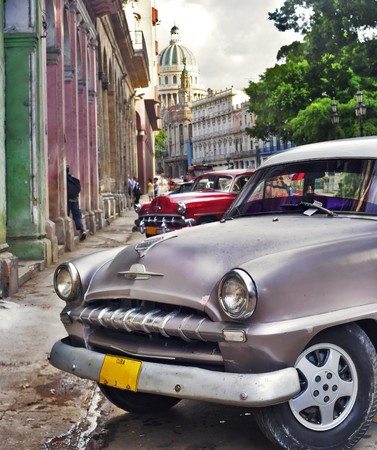 Detail of classic american car with havana buildings in the background