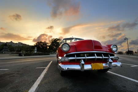 oldtimer: View of red classic vintage american car parked in havana street against sunset sky