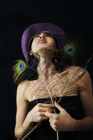 Portrait of young trendy girl holding peacock feathers under disco lights background photo