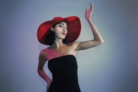 Portrait of young elegant woman wearing black dress and hat photo